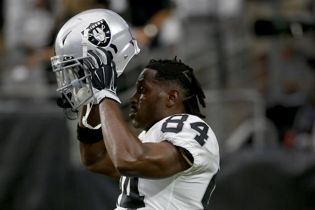 Oakland Raiders wide receiver Antonio Brown (84) puts on his helmet prior to an NFL football game against the Arizona Cardinals, Thursday, Aug. 15, 2019, in Glendale, Ariz. (AP Photo/Rick Scuteri)