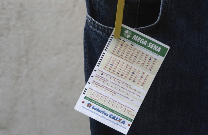 A Mega Sena lottery ticket is displayed in Sao Paulo January 18, 2014. Brazilian police said on Saturday that they had broken up a bank robbery scheme that had diverted 73 million reais ($31 million) from a lottery run by state-owned lender Caixa Economica Federal. The operation, which spanned three states, was the largest fraud in Caixa Economica's history, according to a statement from the federal police. The statement said 70 percent of the stolen funds had been recovered. The money was diverted from Caixa by forging a winning ticket to the Mega-Sena lottery late last year, police said. REUTERS/Nacho Doce (BRAZIL - Tags: BUSINESS CRIME LAW SOCIETY)