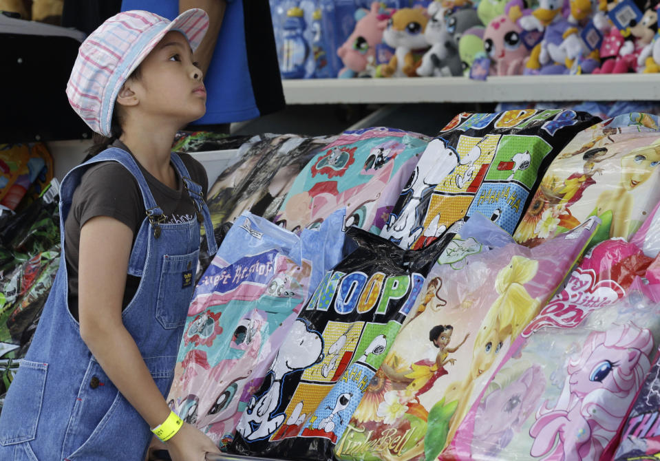"A young girl looks at showbags on offer at the Royal Easter Show in Sydney Friday, April 15, 2011. The Royal Easter Show first started in 1823 is historically an event where ""city meets country"" and the rural industries of Australia can be shown and celebrated once a year. (AP Photo/Rob Griffith)"