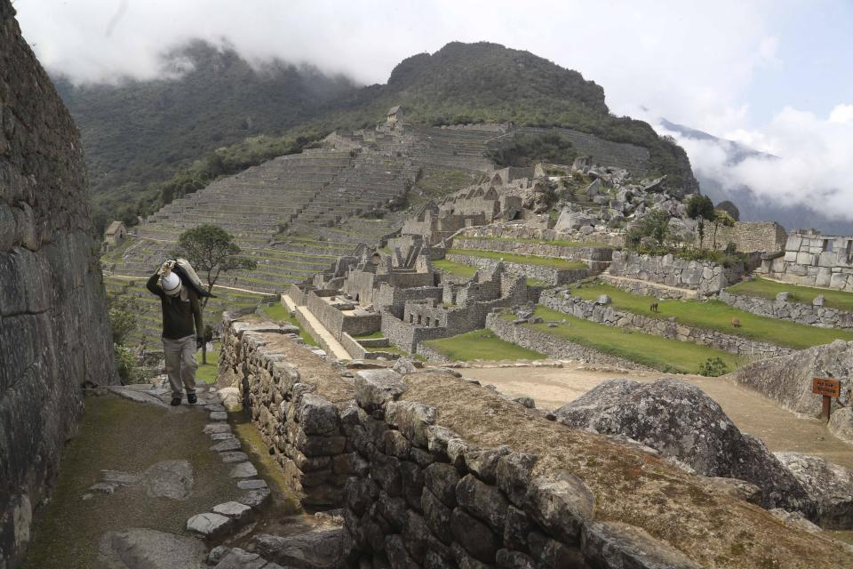 A maintenance worker carries a bag of stones at the Machu Picchu archeological site that's closed to the public amid the COVID-19 pandemic in the department of Cusco, Peru, Tuesday, Oct. 27, 2020. The world-renown Incan citadel of Machu Picchu will reopen to the public on Nov. 1. (AP Photo/Martin Mejia)