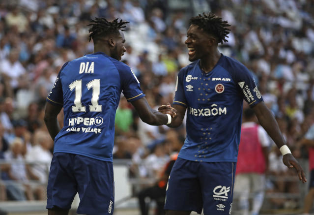 Reims' Boulaye Dia, left, celebrates with Axel Disasi after scoring the opening goal during the French League One soccer match between Marseille and Reims at the Velodrome Stadium in Marseille, France, Saturday, Aug. 10, 2019. (AP Photo/Daniel Cole)