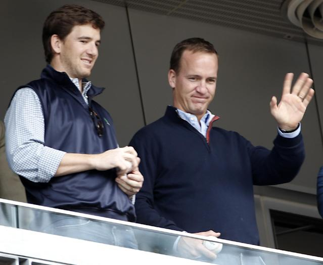 Denver Broncos quarterback Peyton Manning, right, waves to fans as he stands with his brother, New York Giants quarterback Eli Manning, in New York Yankees' Derek Jeter's suite during a baseball game between the Yankees and the Tampa Bay Rays at Yankee Stadium in New York, Sunday, May 4, 2014. (AP Photo/Kathy Willens)
