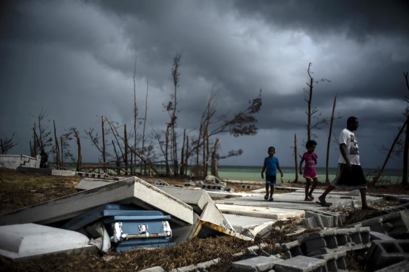 People walk next to a shattered and water-filled coffin lays exposed to the elements in the aftermath of Hurricane Dorian, at the cemetery in Mclean's Town, Grand Bahama, Bahamas, Friday Sept. 13, 2019. (AP Photo/Ramon Espinosa)