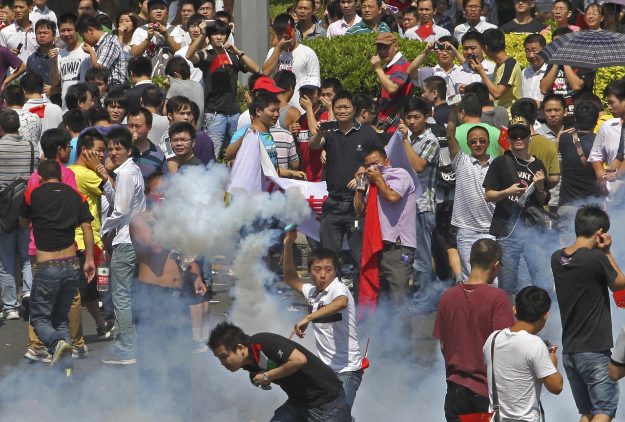 A Chinese demonstrator throws a teargas canister back to riot policemen during a protest against Japan in Shenzhen, China Sunday, Sept. 16, 2012. Protesters in China have begun another day of demonstrations against Japan, after protests over disputed islands spread across numerous cities and at times turned violent. (AP Photo/Apple Daily) HONG KONG OUT, TAIWAN OUT, NO SALES