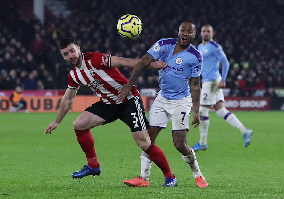Sheffield United's Enda Stevens (left) in action with Manchester City's Raheem Sterling.