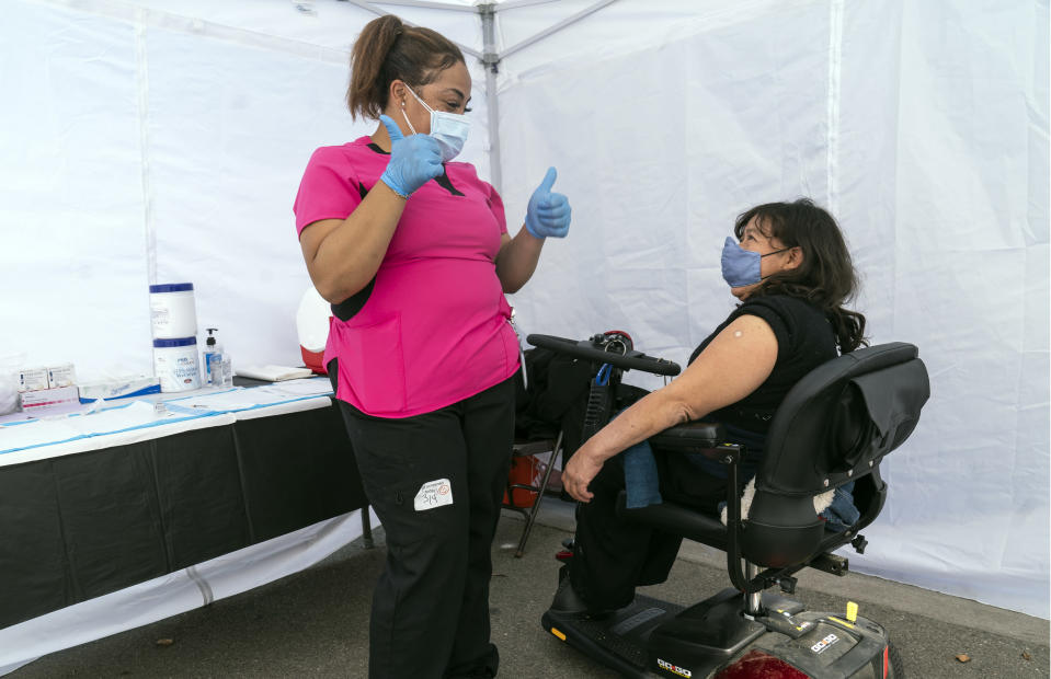 Veronica Lopez, who has Spina bifida, and who is a resident of the 90255 ZIP code, is vaccinated by medical assistant Keyaira Excoe at the St. John's Well Child and Family Center's COVID-19 vaccination site at the East Los Angeles Civic Center in Los Angeles, Thursday, March 4, 2021. California will begin setting aside 40% of all vaccine doses for the state's most vulnerable neighborhoods in an effort to inoculate people most at risk from the coronavirus more quickly. (AP Photo/Damian Dovarganes)