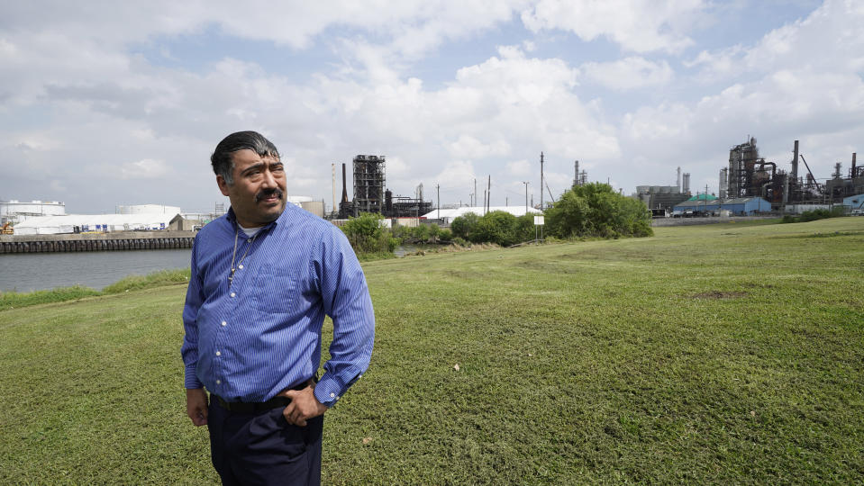 Juan Flores stands in small park near a refinery along the Houston Ship Channel Monday, March 23, 2020, in Houston. Flores is working on a project to install air monitors at schools, not to warn children when the air was too bad to play outside, but alert them when plant emissions were low enough to make that safe. (AP Photo/David J. Phillip)