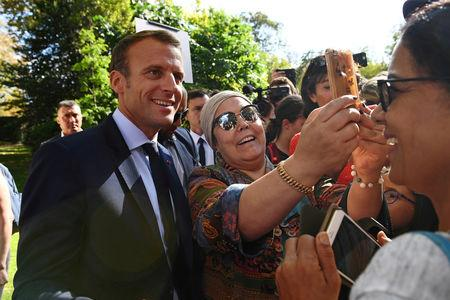 FILE PHOTO: French President Emmanuel Macron poses for a selfie with a woman as visitors are allowed access to the Elysee Palace in Paris, France, September 15, 2018, as part of France's Heritage Days. Picture taken September 15, 2018.  Anne-Christine Poujoulat/Pool via REUTERS/File Photo
