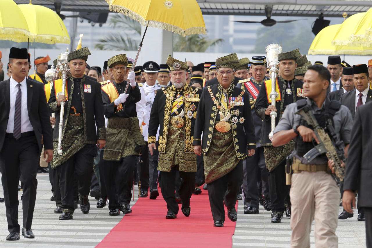 FILE - In this July 17, 2018, file photo, Malaysian King Sultan Muhammad V, center, walks to parliament building for the opening of the 14th parliament session in Kuala Lumpur, Malaysia. Sultan Muhammad V shocked the nation by announcing his abdication in January 2019, days after returning from two months of medical leave. The 49-year-old sultan from eastern Kelantan state only reigned for two years as Malaysia's 15th king and didn't give any reason for quitting. (AP Photo/Yam G-Jun, File)