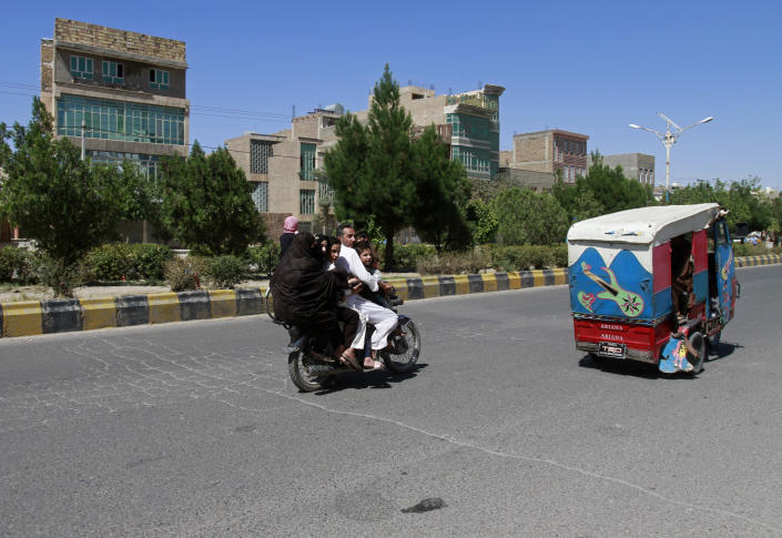 An Afghan family travels on a motorcycle during fighting between Taliban and Afghan security forces in Herat province, west of Kabul, Afghanistan, Sunday, Aug. 1, 2021. (AP Photo/Hamed Sarfarazi)