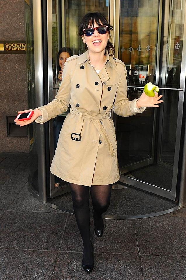 As usual, a trench-wearing Zooey Deschanel looked effortlessly cool while walking out of the the Sirius XM Radio offices in Manhattan smiling -- and snacking on an apple.(09/16/2011)