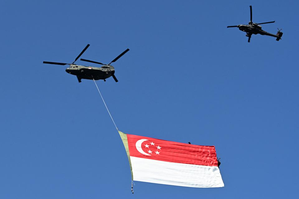 A Republic of Singapore Air Force Chinook helicopter (L) is escorted by an Apache helicopter over the city as they parade the Singapore flag to mark the country's 56th National Day in Singapore on August 9, 2021. (Photo by ROSLAN RAHMAN / AFP) (Photo by ROSLAN RAHMAN/AFP via Getty Images)