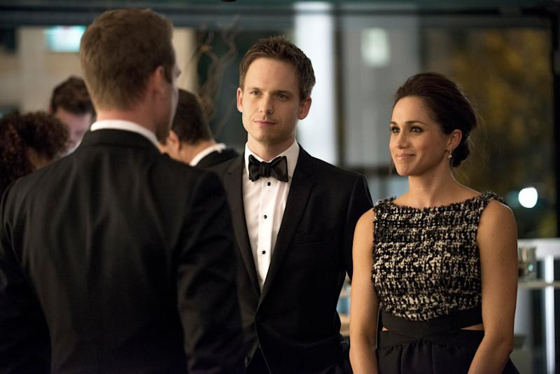 SUITS, (from left): Gabriel Macht (back to camera), Patrick J. Adams, Meghan Markle, 'War', (Season 2, ep. 216, aired Feb. 21, 2013). photo: Christos Kalohoridis / USA Network / Courtesy: Everett Collection