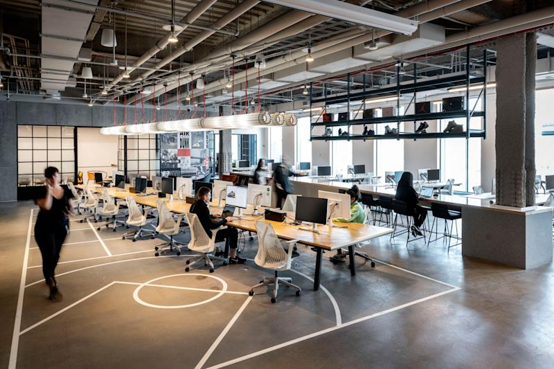 A shot of the open-floor concept at S23NYC, including computers at desks like a standard office but also a floor that resembles a basketball court