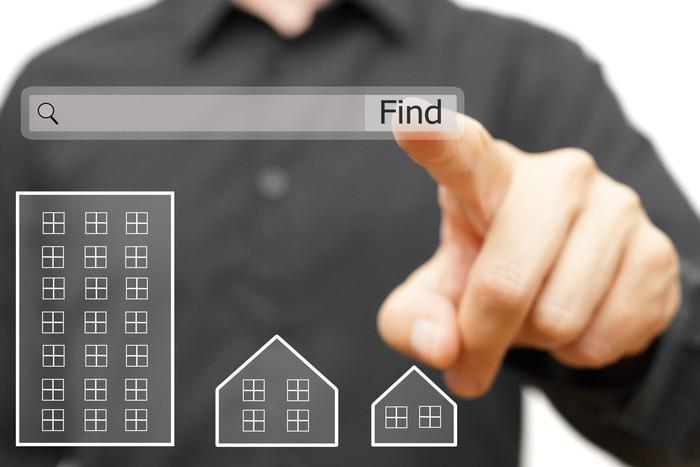 A person pointing to a digital search box above digital houses.