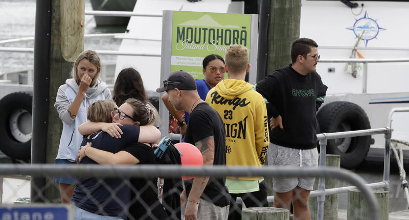 Families of victims of the White Island eruption embrace as they arrive back to the Whakatane wharf following a blessing at sea ahead of the recovery operation off the coast of Whakatane New Zealand, Friday, Dec. 13, 2019. A team of eight New Zealand military specialists landed on White Island early Friday to retrieve the bodies of victims after the Dec. 9 eruption. (AP Photo/Mark Baker)