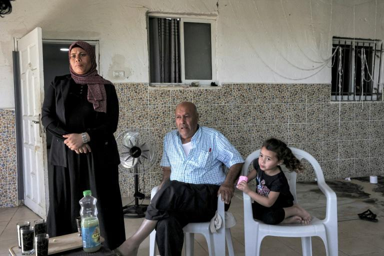 Members of the Abu Qwaider family sit together at their home in the village of Sawaneen, in Israel's southern Negev region