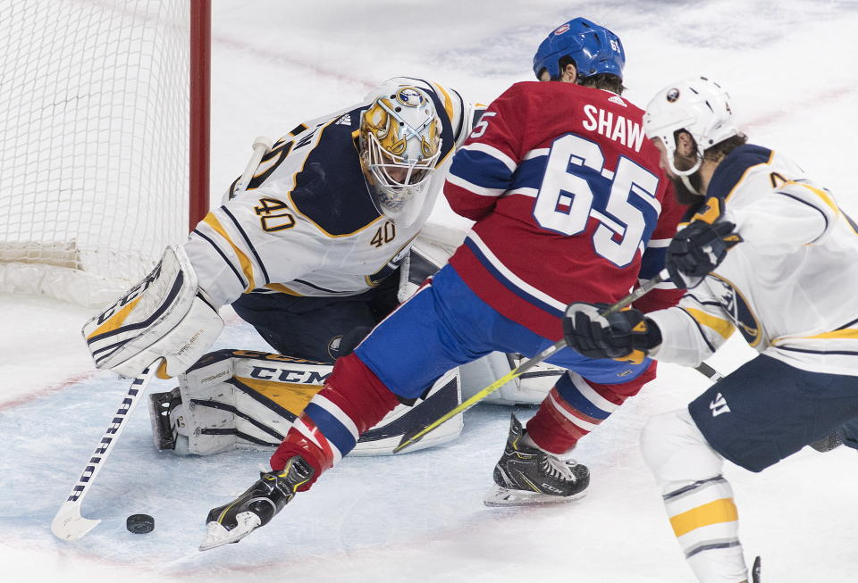 Montreal Canadiens' Andrew Shaw (65) moves in on Buffalo Sabres goaltender Carter Hutton as Sabres' Zach Bogosian defends during first period NHL hockey action in Montreal, Saturday, March 23, 2019. (Graham Hughes/The Canadian Press via AP)
