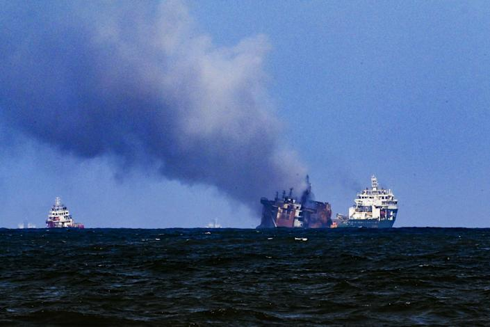 A tugboat (R) from the Dutch salvage firm SMIT tows the fire stricken Singapore-registered container ship MV X-Press Pearl (C) away from the coast of Colombo on June 2, 2021 following Sri Lankan President Gotabaya Rajapaksa's order to move the ship to deeper water to prevent a bigger environmental disaster. / Credit: ISHARA S. KODIKARA/AFP/Getty