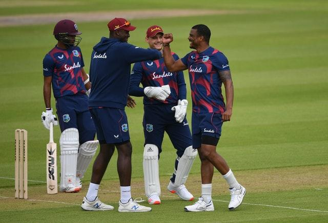 Shannon Gabriel (right) celebrates taking the wicket of John Campbell