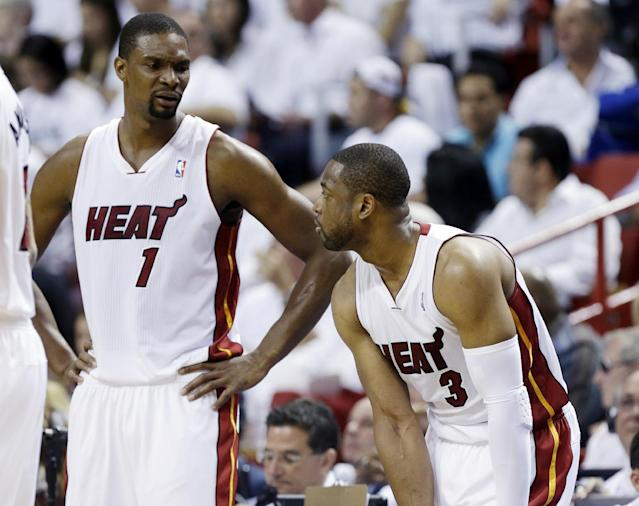 Miami Heat center Chris Bosh (1) and guard Dwyane Wade (3) talk as they fall behind the Indiana Pacers during the first half of Game 3 in the NBA basketball Eastern Conference finals playoff series, Saturday, May 24, 2014, in Miami. (AP Photo/Lynne Sladky)
