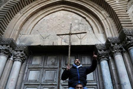 A worshipper holds a cross during a protest in front of the closed doors of the Church of the Holy Sepulchre in Jerusalem's Old City