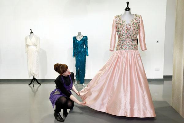 House assistant Lucy Bishop poses with a Catherine Walker Mughal-inspired pink slubbed silk evening gown and bolero worn by Diana, Princess of Wales, at Kerry Taylor Auctions in London March 1, 2013. The gown was worn by Diana during the state visit to India in February 1992. The gown will be auctioned in London on March 19, 2013 and is expected to earn �80,000-�120,000 pounds (U.S. $120,211-180,311). REUTERS/Suzanne Plunkett
