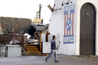 In this March 3, 2020, file photo, a man walks by The Basement East, a live music venue, on March 3, 2020, after a tornado hit Nashville, Tenn. It has been nearly a year since deadly storms tore across Nashville and other parts of Tennessee, killing more than 20 people and damaging more than 140 buildings. (AP Photo/Mark Humphrey, File)