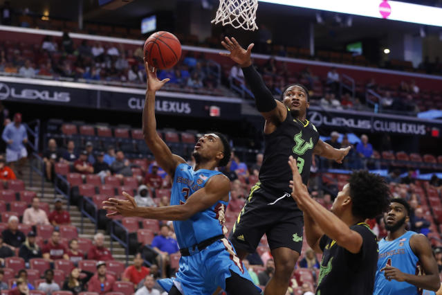 Florida State guard Trent Forrest, left, goes up for a shot against South Florida guards Laquincy Rideau, center, and Xavier Castaneda, foreground, in the first half of an NCAA college basketball game, part of the Orange Bowl Classic tournament, Saturday, Dec. 21, 2019, in Sunrise, Fla. (AP Photo/Wilfredo Lee)