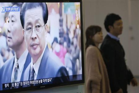 A couple walks past a television showing a report on Jang Song Thaek, North Korean leaders' uncle, at a railway station in Seoul December 3, 2013.