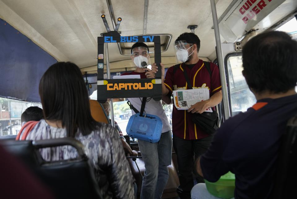 """Juan Pablo Lares, right, holds a cardboard frame in front of his associate Maximiliano Bruzual who reads their newscast """"El Bus TV Capitolio"""" to commuters on a bus in Caracas, Venezuela, Saturday, July 31, 2021. Two decades of governments that see the press as an enemy have pushed Venezuelan journalists to find alternative ways to keep citizens informed. (AP Photo/Ariana Cubillos)"""