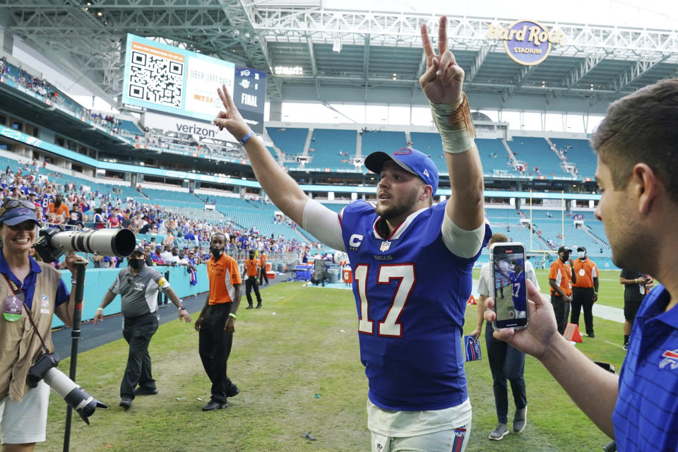 Buffalo Bills quarterback Josh Allen (17) raises his arms at the end of an NFL football game against the Miami Dolphins, Sunday, Sept. 19, 2021, in Miami Gardens, Fla. The Bills defeated the Dolphins 35-0. (AP Photo/Hans Deryk)
