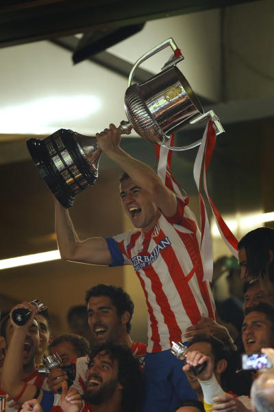 Atletico de Madrid's Gabi lifts the trophy after defeating Real Madrid in the Copa del Rey final soccer match at the Santiago Bernabeu stadium in Madrid, Spain, Friday, May 17, 2013. (AP Photo/Daniel Ochoa de Olza)
