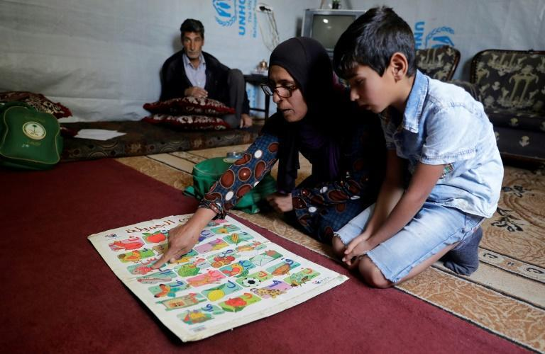Mohammad's mother helps him revise his Arabic lesson after months without school