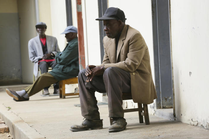 Elderly men sit outside their rooms at the Society for the Destitute Aged care home in Harare's Highfield township, Zimbabwe, Thursday June 24, 2021. The economic ravages of COVID-19 are forcing some families in Zimbabwe to abandon the age old tradition of taking care of the elderly. Zimbabwe's care homes have experienced a 60% increase in admissions since the outbreak of the pandemic in March last year. (AP Photo/Tsvangirayi Mukwazhi)