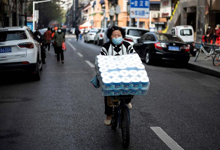 Image: A woman wearing a face mask pedals along a street in Wuhan, in China's central Hubei province (Noel Celis / AFP - Getty Images)