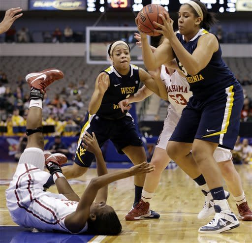 Oklahoma's Sharane Campbell, bottom left, loses control of the ball after falling to the court as West Virginia' Ayana Dunning, top right, gains control in the first half of an NCAA college basketball game in the Big 12 women's tournament Saturday, March 9, 2013, in Dallas. Wester Virginia' Christal Caldwell (1) and Oklahoma' Joanna McFarland (53) watch during the play. (AP Photo/Tony Gutierrez)