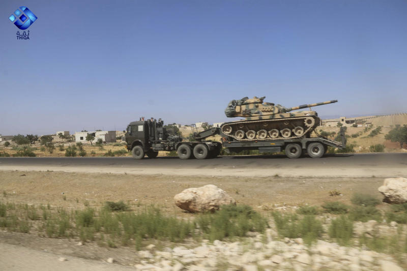 This photo provided by the activist-operated Thiqa News Agency, shows part of a Turkish military convoy heading toward the town of Khan Sheikhoun, a rebel-held northwestern town that's part of a government offensive on the country's last rebel stronghold, in Idlib province, Syria, Monday, Aug. 19, 2019. A Turkish military convoy carrying ammunition crossed into northern Syria Monday and moved south through rebel-held areas before it was stopped by airstrikes that struck near the highway where the convoy was moving, opposition activists said. (Thiqa News Agency via AP)