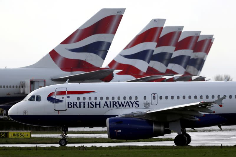FILE PHOTO: BA plane taxis past tail fins of parked aircraft to runway near Terminal 5 at Heathrow Airport