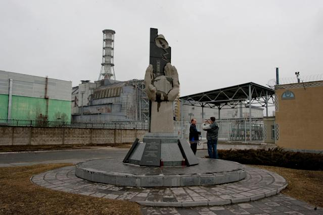 CHERNOBYL, UKRAINE - MARCH 25: Tourists take pictures in front of the destroyed No. 4 nuclear reactor block in the Chernobyl nuclear power plant on March 25, 2011 in Chernobyl, Ukraine. The 25th anniversary of the Chernobyl nuclear disaster is next month. On April 26, 1986, a series of explosions destroyed Chernobyl's reactor No. 4 station causing a nuclear meltdown as firefighters tackled a blaze that burned for 10 days and sent a plume of radiation around the world in the worst-ever civil nuclear disaster. Over fifty people died and more than 130,000 people were evacuated from around the Chernobyl dead zone.. (Photo by Vladimir Simicek - isifa/Getty Images)