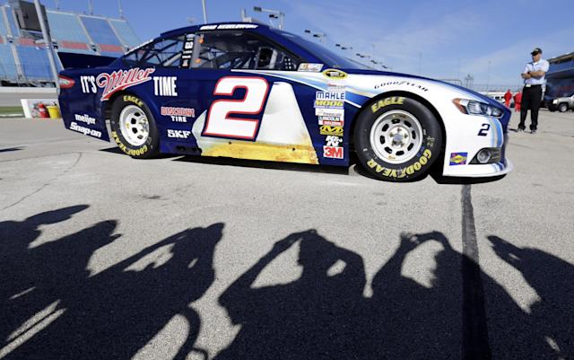 NASCAR fans take photos of Brad Keselowski's car while Brad Keselowski drives his car during practice for the NASCAR Sprint Cup Series auto race at Chicagoland Speedway in Joliet, Ill., Saturday, Sept. 14, 2013. (AP Photo/Nam Y. Huh)