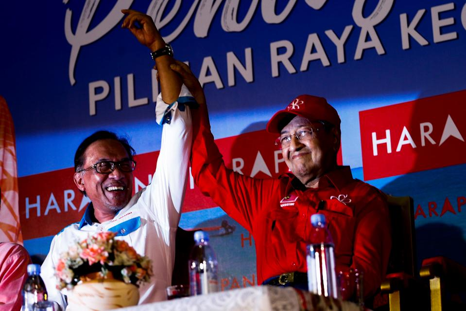 PORT DICKSON, MALAYSIA - OCTOBER 8: Malaysian Prime Minister Tun Mahathir Mohamad (R) raises up Anwar Ibrahim's hand during by-election campaign, in Port Dickson, Malaysia on October 8, 2018. The support, given by Mahathir Mohamad as part of the agreement in the Pakatan Harapan Coalition (Alliance of Hope), decision to make him a Prime Minister within 2 years.  (Photo by Adli Ghazali/Anadolu Agency/Getty Images)
