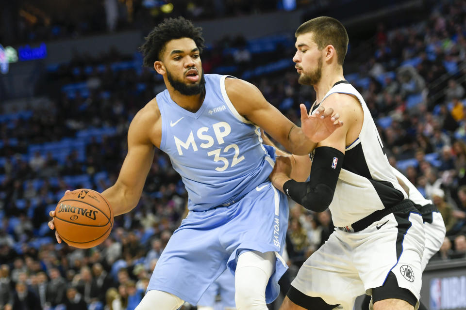 Minnesota Timberwolves center Karl-Anthony Towns (32) tries to drive past Los Angeles Clippers center Ivica Zubac during the first half of an NBA basketball game Friday, Dec. 13, 2019, in Minneapolis. (AP Photo/Craig Lassig)