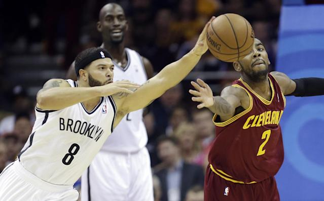 Brooklyn Nets' Deron Williams (8) and Cleveland Cavaliers' Kyrie Irving (2) battle for a loose ball during the first quarter of an NBA basketball game Wednesday, Oct. 30, 2013, in Cleveland. (AP Photo/Tony Dejak)