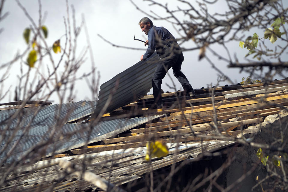 A man dismantles the roof of his house in an area once occupied by Armenian forces but soon to be turned over to Azerbaijan, in Karvachar, the separatist region of Nagorno-Karabakh, on Friday, Nov. 13, 2020. Under an agreement ending weeks of intense fighting over the Nagorno-Karabakh region, some Armenian-held territories adjacent to the region are passing to Azerbaijan. (AP Photo/Dmitry Lovetsky)