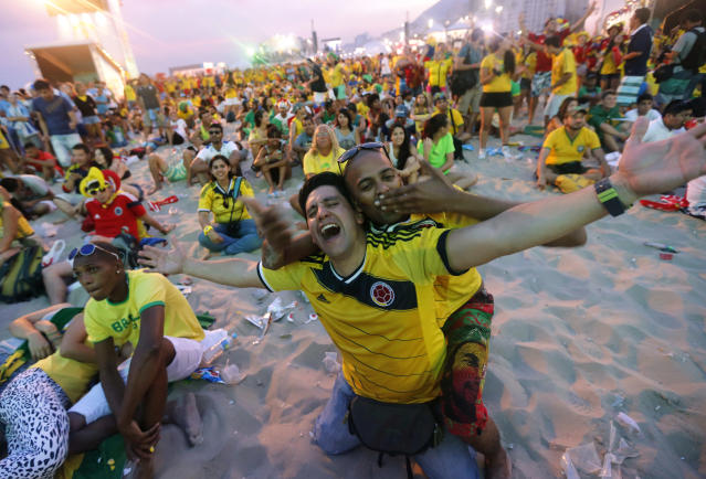 FILE - In this June 28, 2014, file photo, Colombia soccer fans celebrate a goal against Uruguay as they watch the World Cup round of 16 match inside the FIFA Fan Fest area on Copacabana beach in Rio de Janeiro, Brazil. Not since Colombia drubbed Argentina 5-0 in a 1993 World Cup qualifier has the South American nation of 48 million been so enthralled by the beautiful game. (AP Photo/Silvia Izquierdo,File)