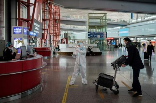 Workers in protective gear greet a passenger in a near-empty arrivals hall at Beijing Capital Airport