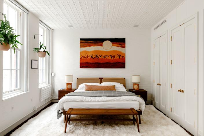 """The focal piece of Harbour's bedroom is a painting on plywood by artist Kevin Kearns. """"It feels kind of grand and epic in a certain way. I really like that,"""" he says. Interior designer Kyle O'Donnell sourced the Semigood Design bed via 1stdibs and topped it with linens by Matteo."""