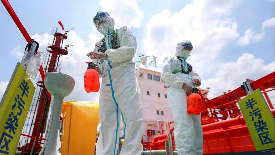 Police officers wearing protective gear against the spread of Covid-19 spray disinfectant at Nanjing port in China`s eastern Jiangsu province on 4 August 2021.