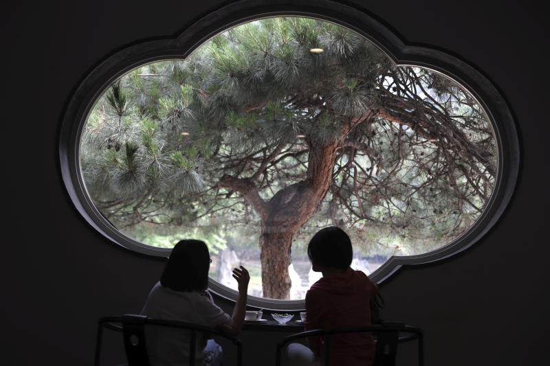 Visitors enjoy the scene from a window of the Xiangshan hotel designed by Chinese-American architect I.M. Pei and built in 1982 in Beijing, China on Friday, May 17, 2019. Pei, the globe-trotting architect who revived the Louvre museum in Paris with a giant glass pyramid and captured the spirit of rebellion at the multi-shaped Rock and Roll Hall of Fame, has died at age 102, a spokesman confirmed Thursday. (AP Photos/Ng Han Guan)